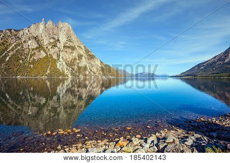 The concept of exotic and extreme tourism. The mirror water of the lake reflects sharp peaks and rocks. Pyramidal mountain in San Carlos de Bariloche
