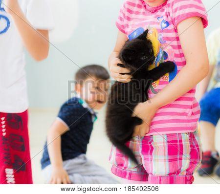 Eskisehir, Turkey - May 05, 2017: Preschool Little Girl Holding A Black Kitten In Her Hands In A Cla