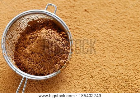 Cocoa powder in a sieve on a table
