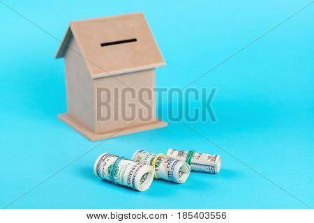 The concept of financial savings to buy a house. Money box dollars in rolls isolated on the blue background.