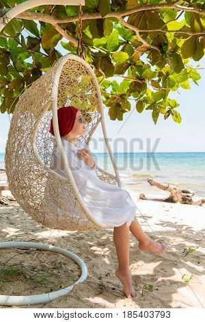 Young beautiful woman enjoying her time at tropical tourist resort beach
