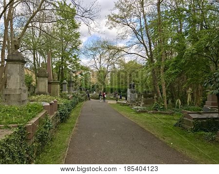LONDON - APRIL 23, 2017: People visit the gravestone of Karl Marx in Highgate Cemetery, Highgate, North London, UK. The cemetery is the resting place of many famous people and is a popular attraction.