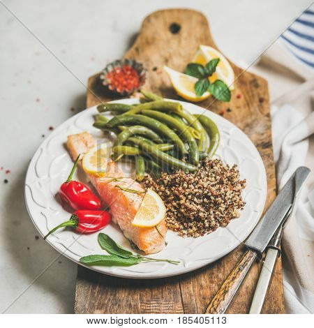 Healthy protein rich dinner plate. Oven roasted salmon fillet with multicolored quinoa, chilli pepper and poached green beans on rustic wooden board over grey marble background, square crop. Diet food