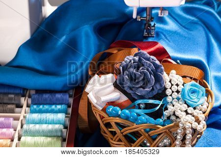 Sewing accessories, colorful thread spools, blue silk fabric, decorations and sewing machine, closeup view