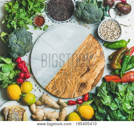 Clean eating healthy cooking ingredients. Vegetables, beans, grains, greens, fruit, spices over grey background, empty marble and wooden board in center with copy space, top view. Diet food concept