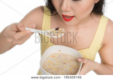 Asian Woman Eating Bowl Of Cereal Or Muesli For Breakfast