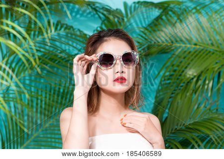Colorful portrait of young attractive asian woman in sexy dress and wearing sunglass over blue background. Summer beauty concept