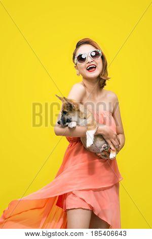 Beautiful Young Asian Woman In Nice Spring Dress, Posing In Studio With Corgi Puppy. Fashion Photo.