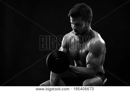 Monochrome studio shot of a young handsome male bodybuilder lifting weights working out with dumbbells copyspace biceps body torso lifestyle sportive masculine brutal strong power activity concept.