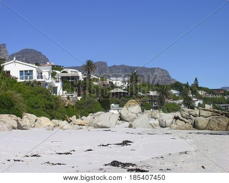 CLIFTON, CAPE TOWN SOUTH AFRICA, LANDSCAPE, BEACH,HOUSES AND VEGETATION IN THE FORE GROUND AND A  MOUNTAIN IN THE BACK GROUND 22zxc