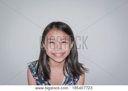 Selective Focus Beautiful Little Girl Smiling And Showing Confidence On Gray Background. Concept Kid