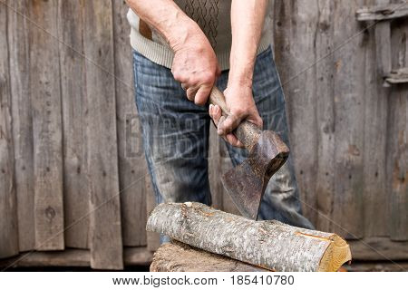 Worker, An Elderly Man With An Old Axe Chops Firewood. Forced To Work In Retirement . Employee .