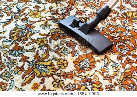 Cleaning old carpet with a vacuum cleaner with a black nozzle .