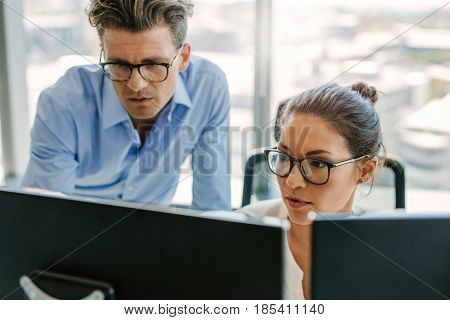 Shot of business man and woman at work desk looking at computer monitor. Focused business team working together in office.