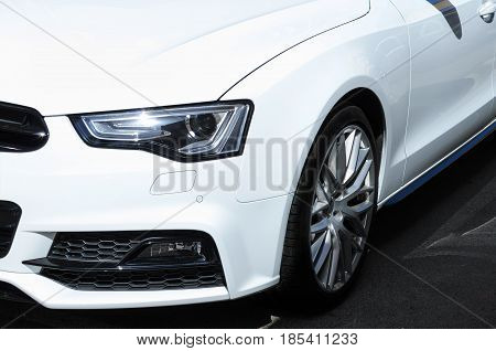 The headlamp of the new clean white sports car is of aggressive form with a part of the bonnet and black wheel bumper and partronik.