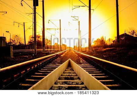 Railway - Railroad at sunset with sun Rails and electric lines in yellow light