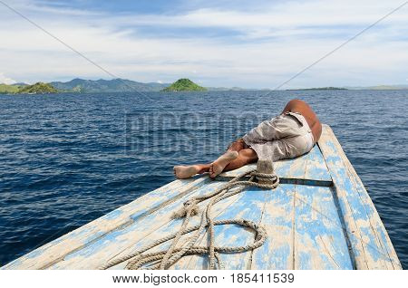 Indonesian sailor resting on the bow of his ship in transit to islands Komodo