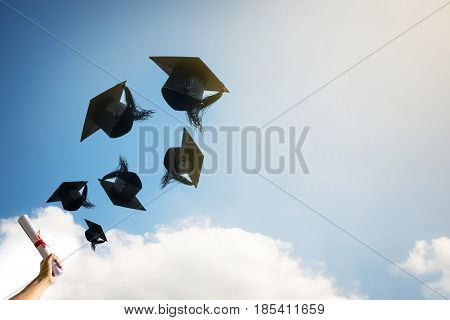 Graduates hands throwing graduation hats in sky