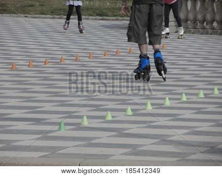 Legs of guy on inline skates . Inline skater and slalom cones