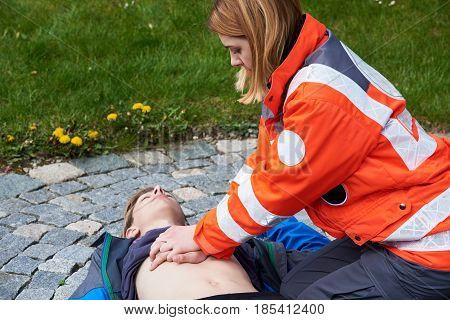 Professional paramedic giving unconscious young man first aid