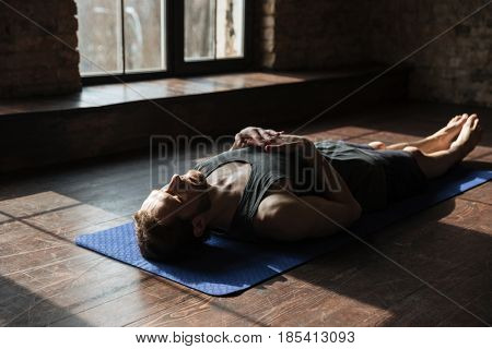 Photo of handsome young strong sportsman in gym lies on floor with eyes closed.