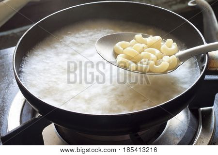 Boil macaroni in pan in kitchen room.