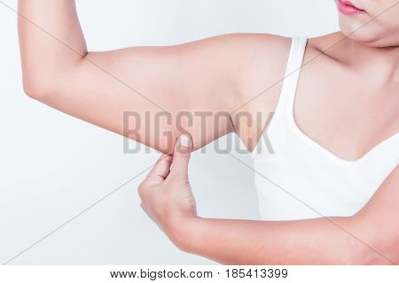 asian woman checking her upper arm on white background