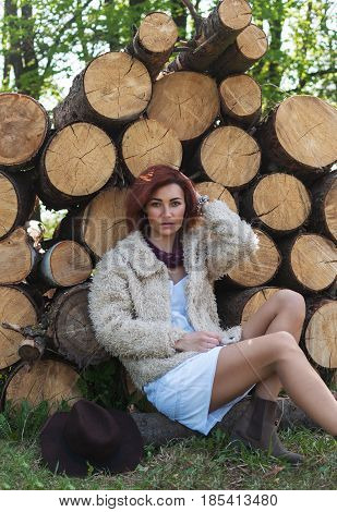 portrait of beautiful redhaired girl in a fur coat sitting on logs.