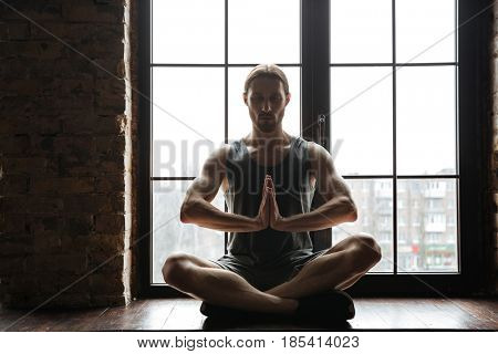 Portrait of a healthy young sportsman meditating in lotus pose with eyes closed while sitting on the windowsill at the gym