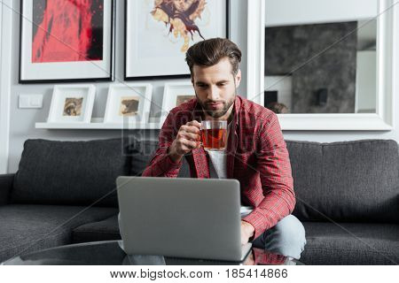 Photo of concentrated young bearded man sitting at home indoors while using laptop computer. Looking aside.