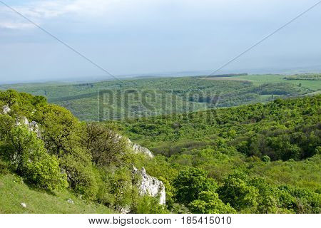 View of the hilly landscape of Palava with forests rocks in South Moravia under a blue sky with clouds