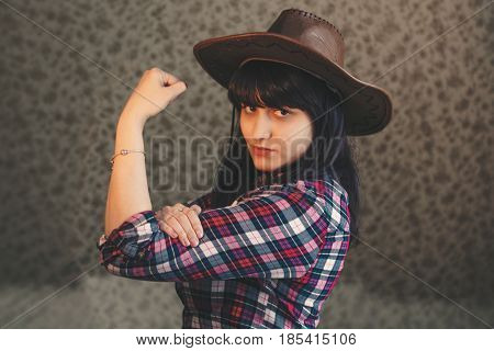 retro toned photo of young girl in a cowboy hat shows her biceps.