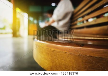 young man sitting waiting for train blurred background.