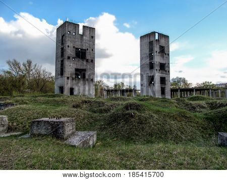 Two half-ruined towers in the wasteland. Two Unfinished high-rise buildings against the blue sky on a cloudy day