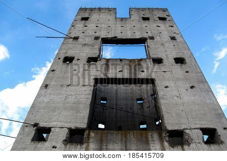 A lonely gray wall against the blue sky. Concrete wall with the holes in which the sky shines