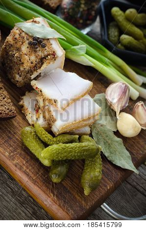 Salted lard with spices vegetables and brown bread.