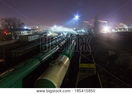 Night view from above on the railway. Commodity trains, freight wagons and cisterns