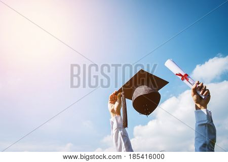Graduate put hands up and celebrating with certificate and hat in hand and feeling so happiness in Commencement day.
