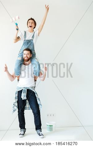 Full length portrait of a happy cheerful couple renovating their house walls together