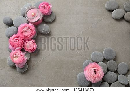 ranunculus and pile of gray stone ,candle on gray background