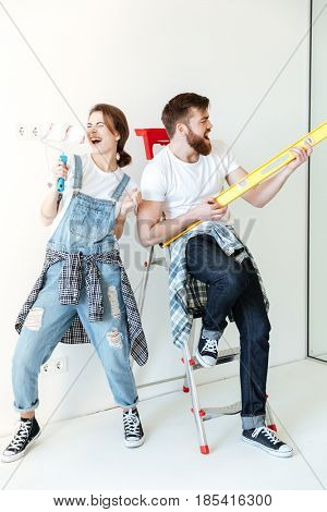 Full length portrait of a happy joyful couple holding work tools and having fun while having a break in repairing their house