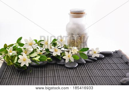 branch gardenia closeup with pile of black stones ,with bottle on mat