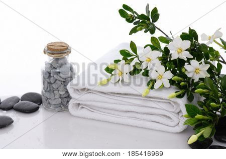Spa setting with branch gardenia on towel, ,stones in bottle