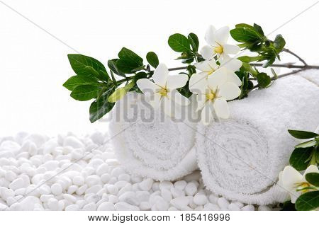 branch gardenia with rolled towel closeup on pile of white stones,