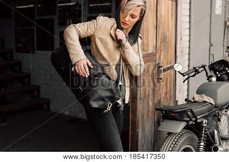 A young woman with a leather bag near the garage. A woman in a leather jacket. Motorcycle near the garage. Leather bag. Motorcycle