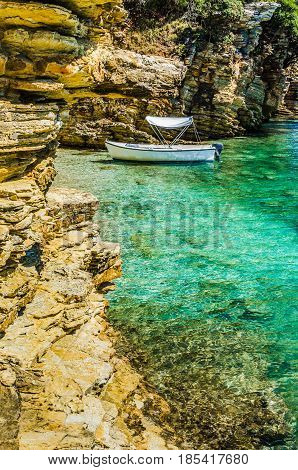 White boat in small cute azure bay surrounded by lime stone cliffs in Corfu island, Greece.