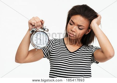 Portrait of an upset frustrated african girl looking at alarm clock isolated over white background