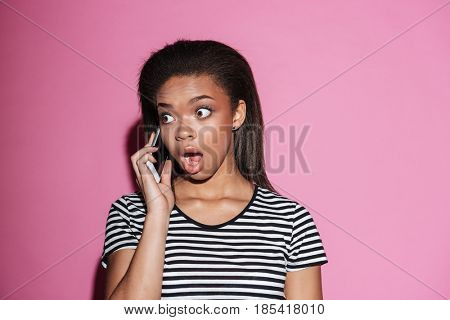 Portrait of a shocked young african woman talking on mobile phone and looking away isolated over pink background