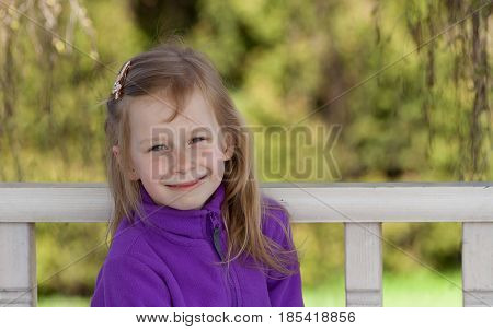 portrait, little girl seven years old, in botanical garden, looking at the camera, long blond wheaten hair, smiling, photo up to the waist, against a wooden white fence and green foliage, lilac jacket