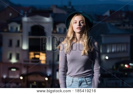 woman portrait in the light of the street lamps girl with hat in profile against the background of the city at night copy space motion effect